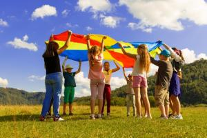 A group of children playing with a rainbow parachute