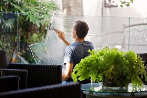 Man in Grey Shirt Cleaning Windows