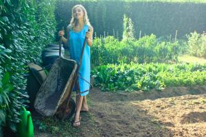 Woman wearing blue dress pushing wheelbarrow in outdoor garden