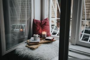 pillow, coffee, and candles displayed in front of a window